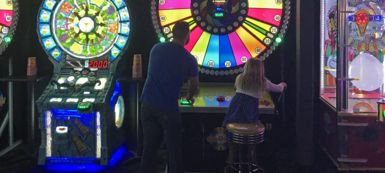 Dad and daughter playing spinning wheel at Dave & Buster's in Overland Park