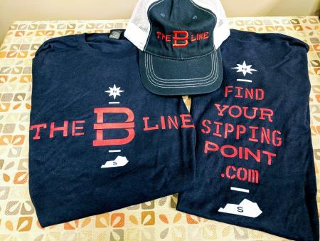 Some of the free bourbon swag people get for completing the B-Line Bourbon trail in NKY. Blue, white and red t-shirts and a hat that have the words The B-Line, Find Your Sipping Point