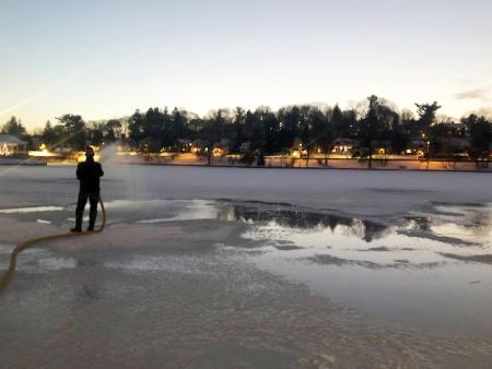 Man with hose making ice to freeze over Hiawatha Lake