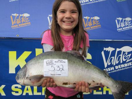 A girl holds up a pink salmon