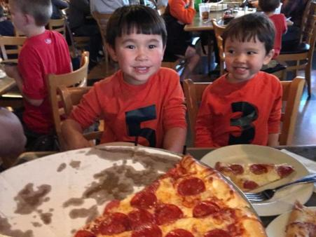 two kids smiling while eating pepperoni pizza at deweys