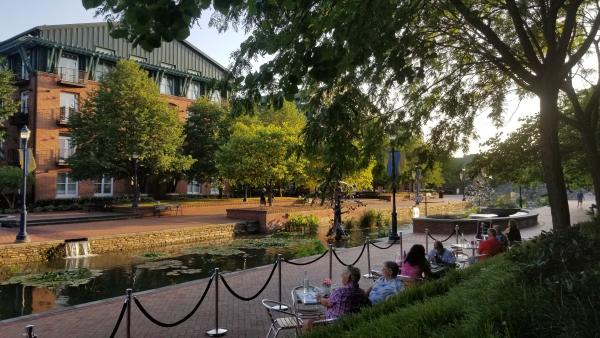 People dining outdoors at The Wine Kitchen overlooking Carroll Creek Park