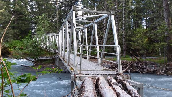 a metal and wood bridge over a creek