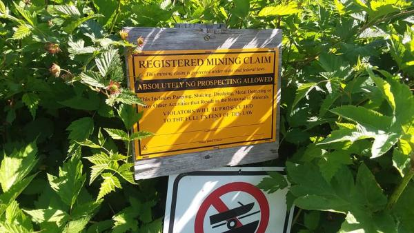 """a sign stating """"REGISTERED MINING CLAIM"""" along a hiking trail"""
