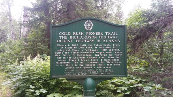 a sign for the Gold Rush Pioneers Trail in Valdez, Alaska. Trees in background