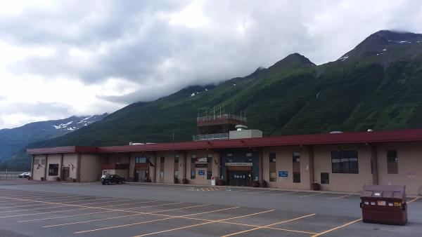 a small airport on a cloudy day; mountains in background