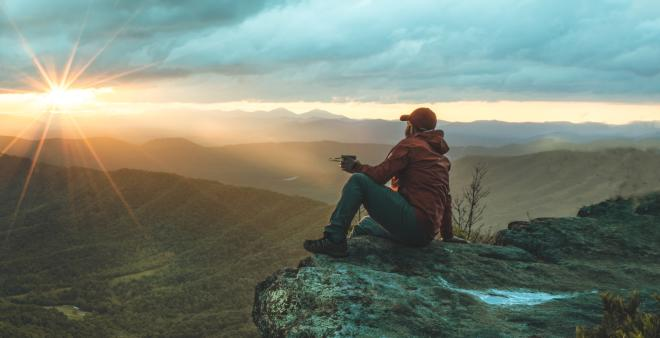 A hiker watching the sunset at McAfee Knob near Roanoke, Virginia