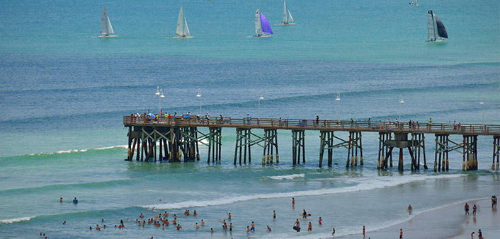 Daytona Beach Pier is a picturesque spot with people fishing, beach goers and sail boats on the horizon