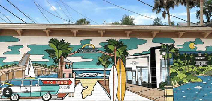 A mural in New Smyrna Beach features a classic car, the beach and surfboards