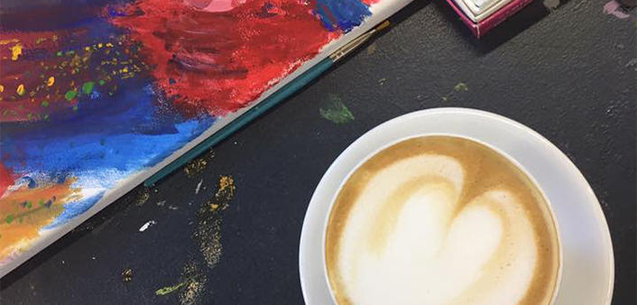 A cup of cappuccino and art supplies at Frame of Mind Art Gallery in Ormond Beach