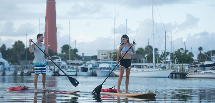 A couple paddleboards at Ponce Inlet with views of the marina and Ponce Inlet Lighthouse
