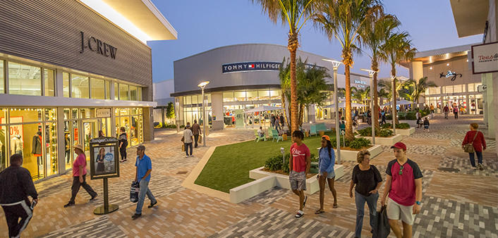 Shoppers stroll Tanger Outlet Daytona Beach at night