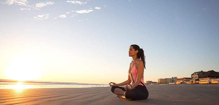 A woman is enjoying yoga at sunrise on Daytona Beach