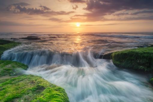 Water Flowing Over Coquina Rocks at Sunset in Kure Beach
