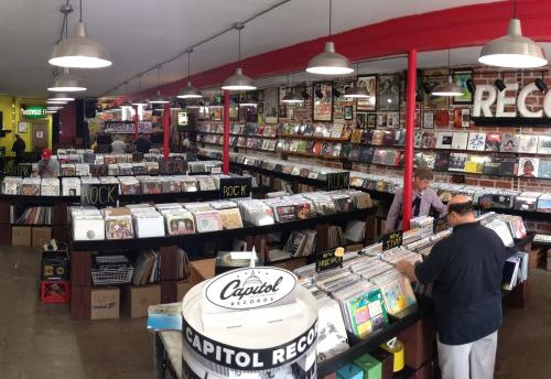 View of aisles and shoppers inside Used Kids record store