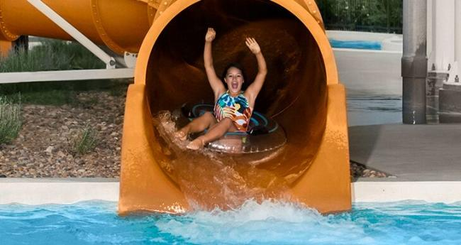A girl gets ready to exit a water slide into a pool while riding an inflatable tube at the Wichita YMCA