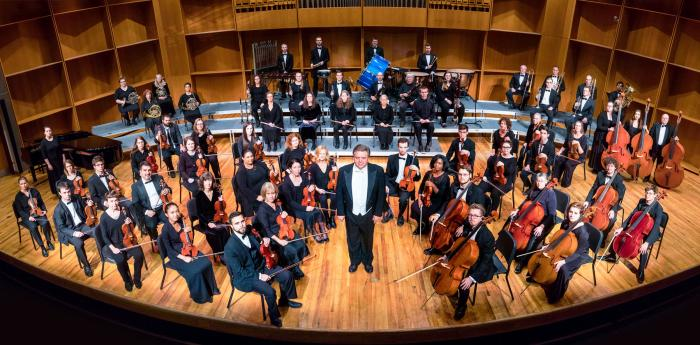 A symphony orchestra, dressed and posing for the camera