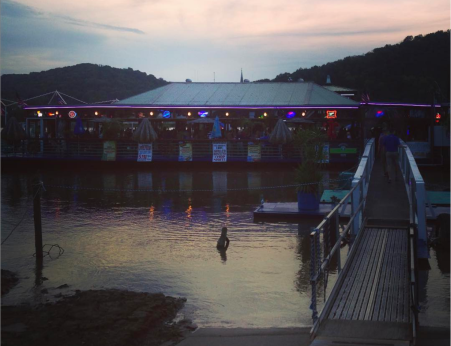 photo of sun setting on ohio river behind the floating restaurant ludlow bromley yacht club