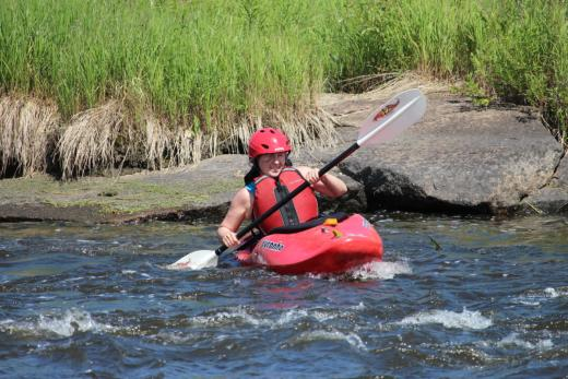 Carol in a kayak turning out into the moving water.