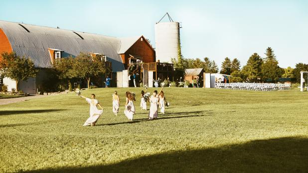 Braidmaids running through lawn at Hayloft on the Arch
