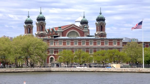 Buildings and American flag on waterfront of Ellis Island