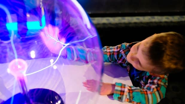 Young boy touches an orb at the Buffalo Science Museum