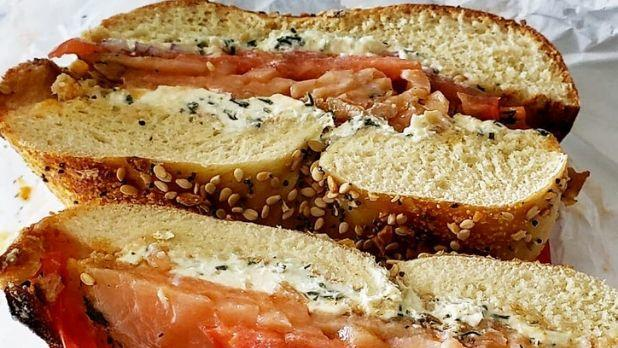 A photo of a bagel cut in half with cream cheese filling and salmon slices