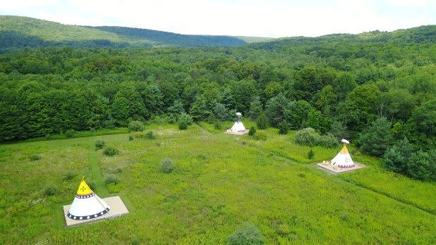 Three tents spread out in a valley in the mountains at Mountain Horse Farm B&B and Wellness Retreat