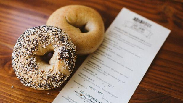 A photo of a plain bagel and an everything bagel on a table next to the Breadhive menu