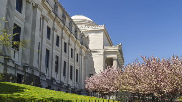 The outside of the Brooklyn Museum with cherry blossom trees at right
