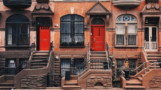 The entrances and façades of three Harlem brownstones.