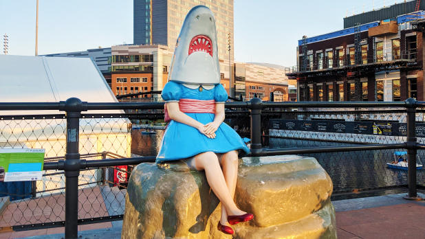 a girl in a dress with a shark head sitting on a rock at Canalside