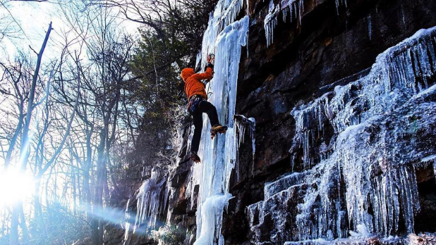 An ice climber scaling an ice-covered rock in the 'Gunks