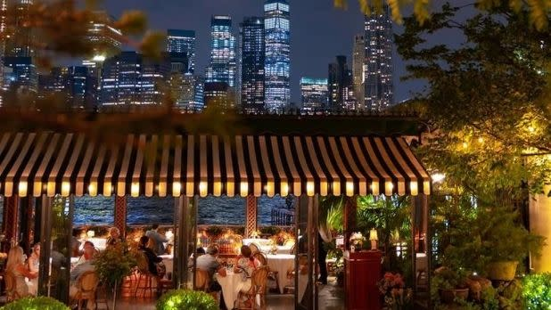 Diners on the patio of Brooklyn's River Cafe with Manhattan's skyline in the background