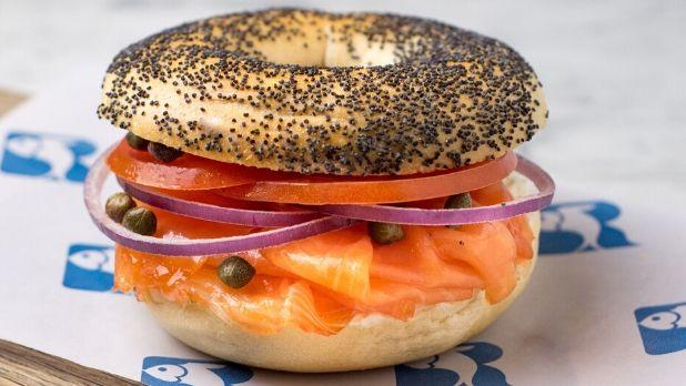 A photo of a poppy seed bagel with salmon onions and tomato on a Russ and Daughters parchment paper