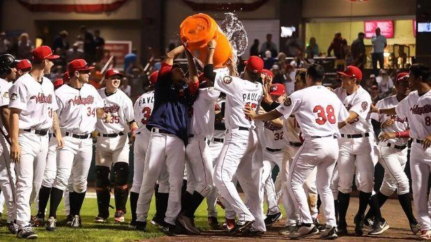 A picture of the Tri-City Valley Cats on the field pouring a cooler of water on their coach