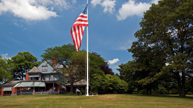 The lawn in front of the Sagamore Hill National Historic Site showing the exterior of the building an an American flag
