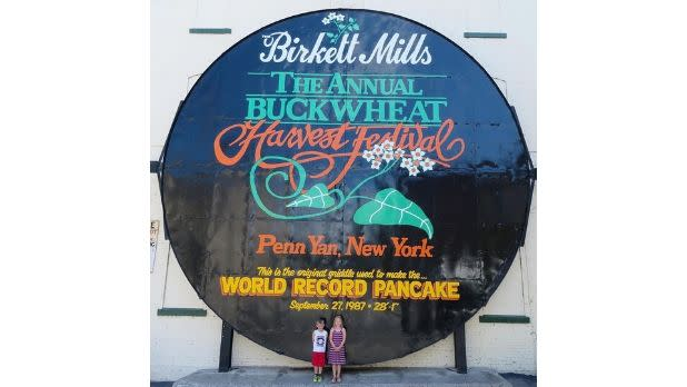 Two small kids standing in front of the world's largest pancake griddle