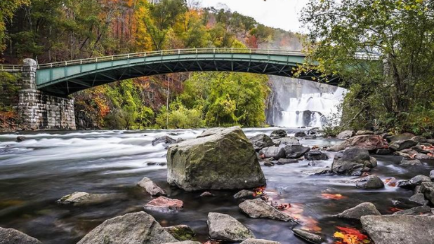 A view of a bridge and water flowing on rocks with the New Croton Dam waterfall in the background