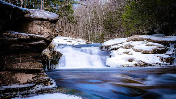 A snowy day at Kaaterskill Falls with frozen water running onto rocks and snow