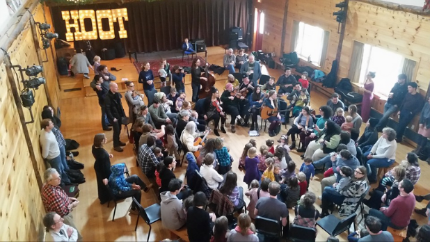 A photo of people gathered in a circle celebrating and having fun at the Winter Hoot in the Catskills