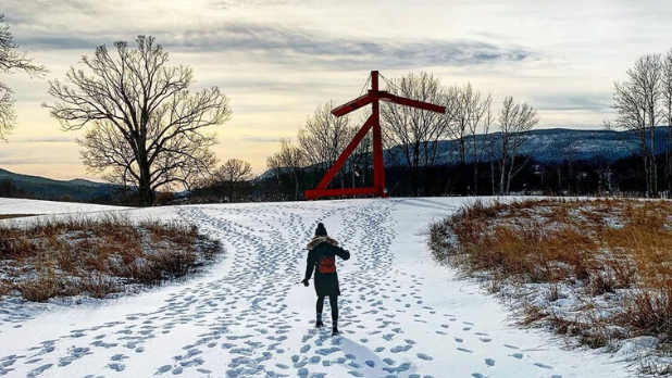 A photo of a woman walking up to a sculpture at Storm King Art Center in the winter