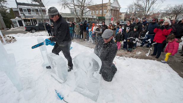 A photo of two men sawing ice at the winter festival HarborFrost in Sag Harbor