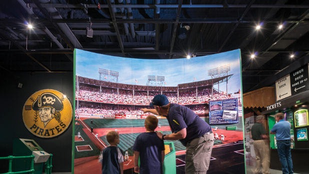 A picture of a dad showing his kids the Baseball Hall of Fame