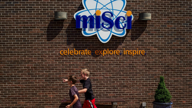 A photo of two children running under the miSci (the Museum of Innovation and Science) sign