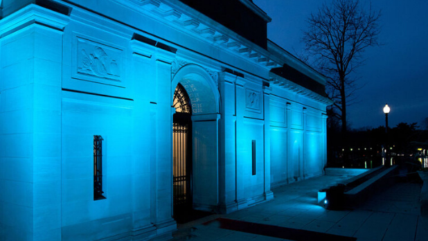 A photo of the exterior of The Heckscher Museum of Art which is lit blue
