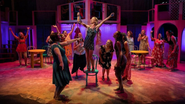 A photo of a girl performing on a chair surrounded by cast mates on stage