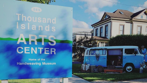 A photo of the sign of the Thousand Islands Art Center with a blue van in the background