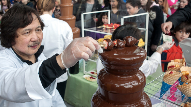 A man dips three strawberries on a stick into a chocolate fountain