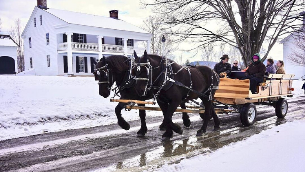 A family riding is a horse drawn carriage during the winter season